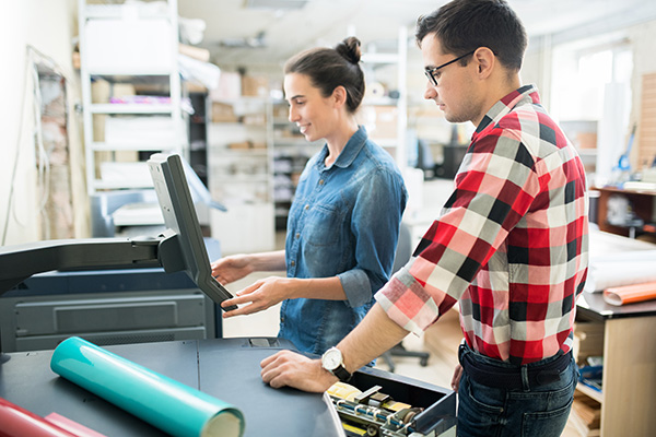 Smiling attractive young lady in casual shirt viewing information on monitor of printer while choosing print options with colleague in printing house