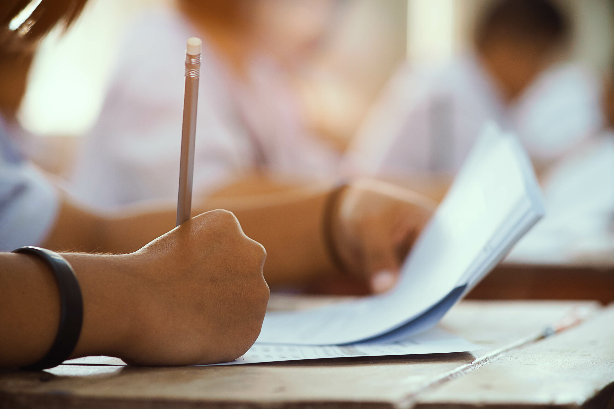 Closeup to hand of student  holding pencil and taking exam in classroom with stress for education test.